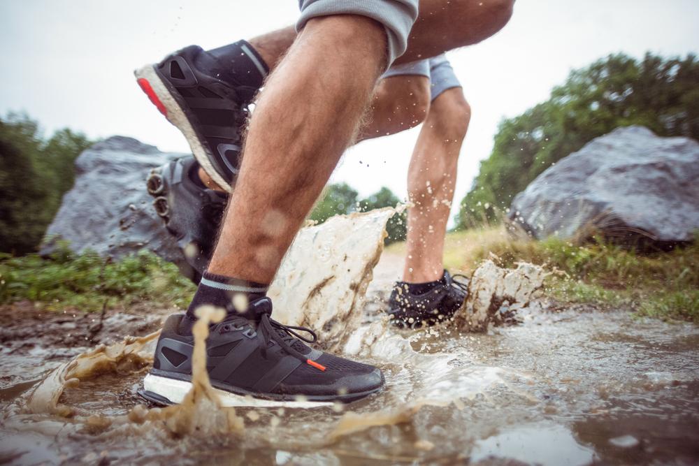 men walking in muddy puddles